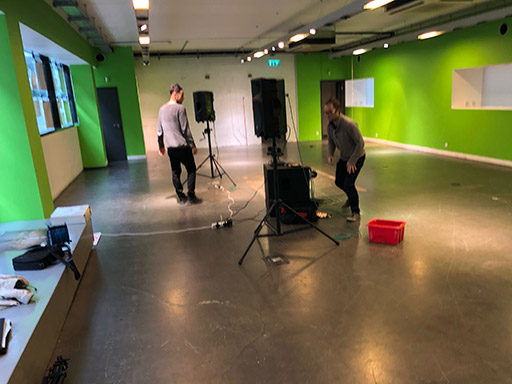 The camera shakes to two loudspeakers in the middle of a large, bright green room.