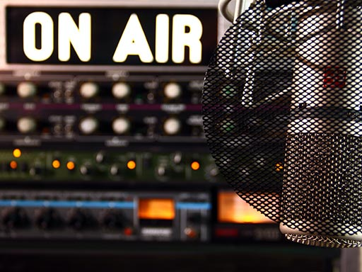 "An ""on air"" sign and microphone inside a studio."