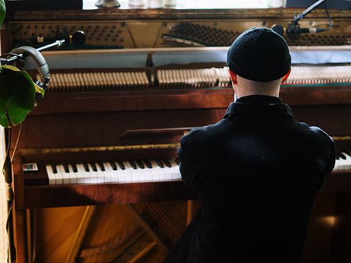 A man in a beanie hat plays a brown acoustic piano.
