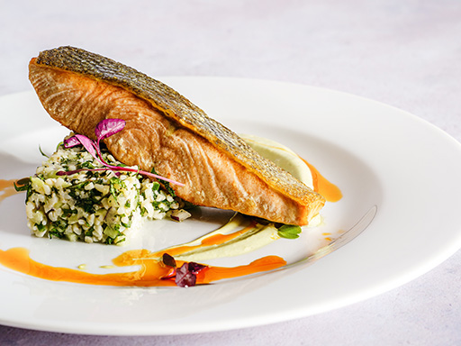 Pan fried salmon on a bed of herby cous-cous.