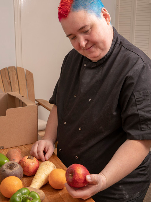 A person with red and blue hair who likes food inspects the contents of a fruit and veg box.