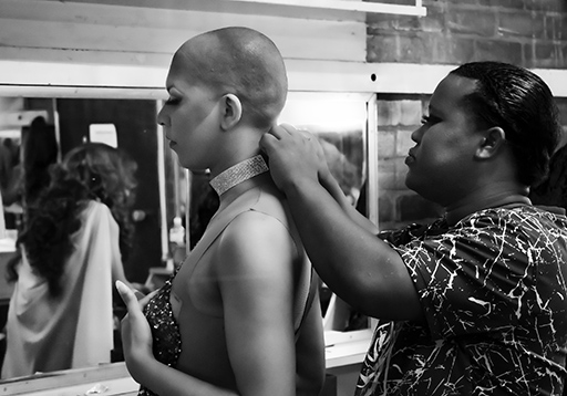 A black woman helps a drag queen with shaved hair and long lashes fix a sparkly choker around his elegant neck.