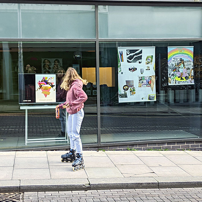 A woman on roller-blades looks at some of the art installed in The Ledward Centre windows.