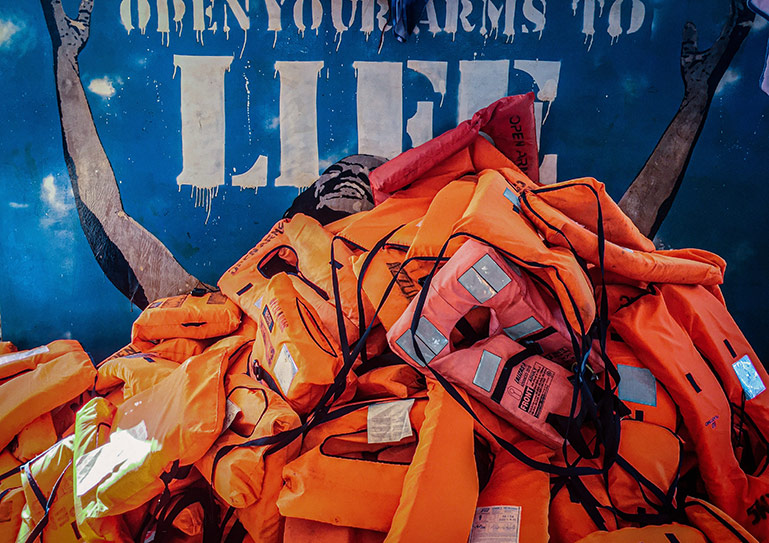 """A pile of day-glow orange lifejackets. The blue background is stencileed witht he words """"open your arms to life"""" and a person of colour raises their arms and looks to the slogan."""